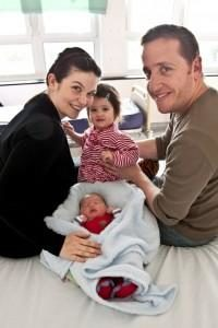 Family smiling with newborn baby