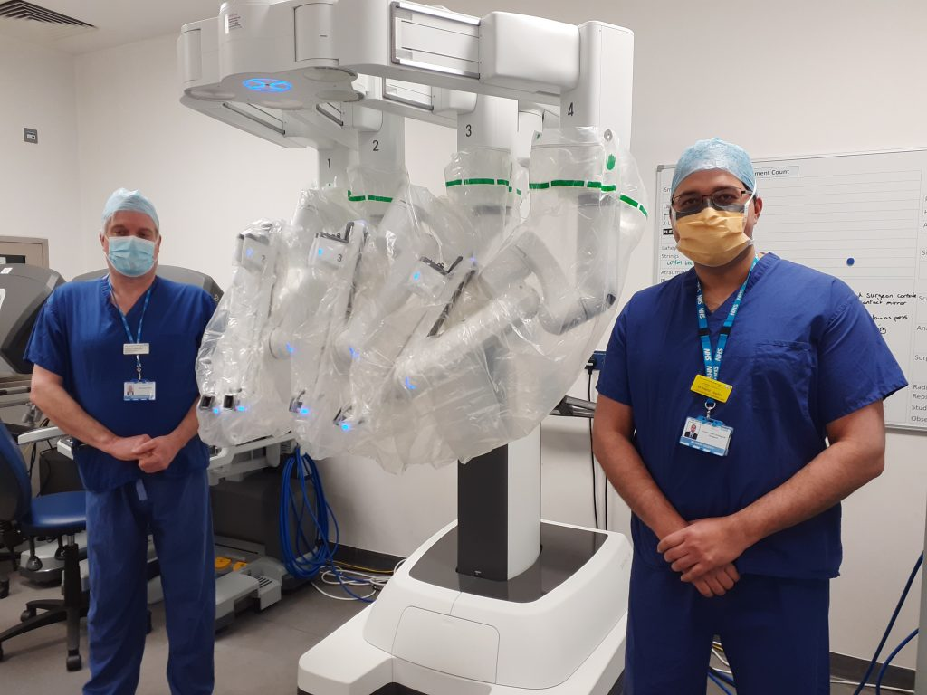 Richard Hammond, East and North Hertfordshire NHS Trust's managing director for planned care, pictured with urology consultant Mr Nikhil Vasdev next to the robot on the day of the first operation