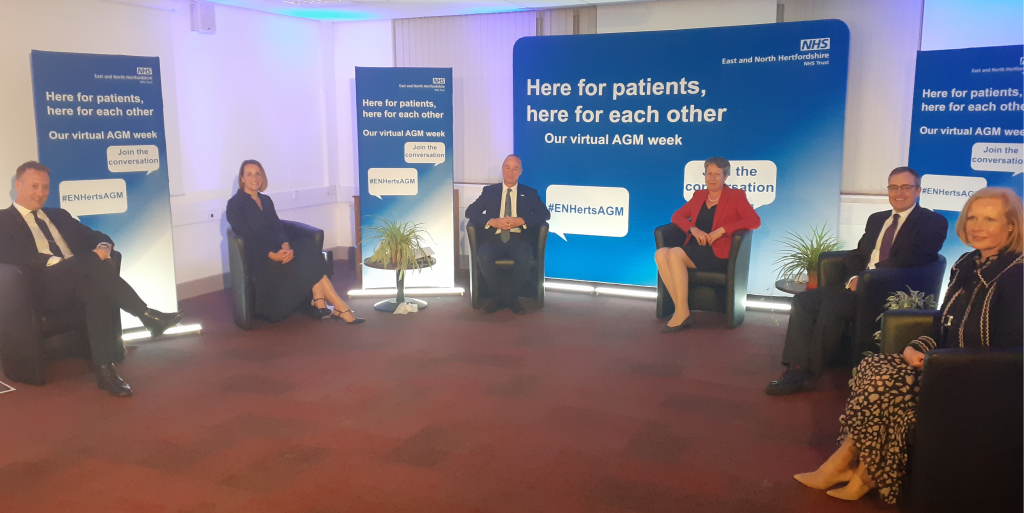 Members of the Trust's executive team sitting in socially-distanced seats in a semi-circle, with banners reading 'Here for patients, here for each other - our virtual AGM week' behind them.