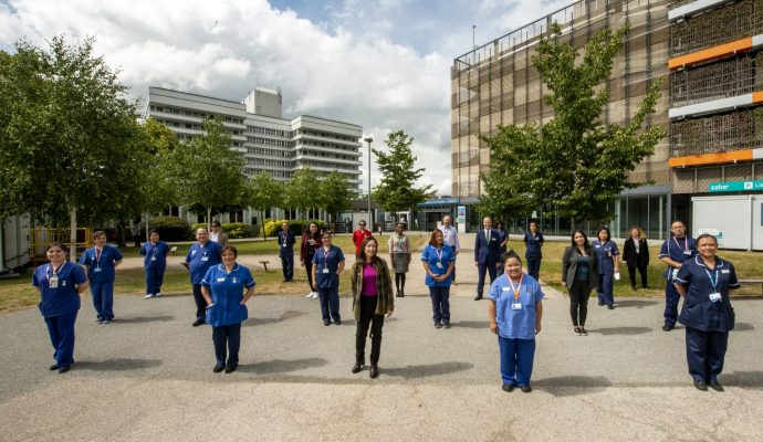 Members of staff standing outside the plaza area of Lister Hospital in Stevenage.