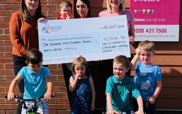 Adults and children holding a cheque for the co-operative childcare